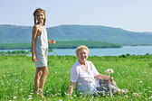 Great grandmother and great granddaughter in meadow — Stock Photo