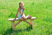 Preteen girl on bench in grass — Stock Photo