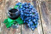 Grapes on a old wooden table and a glass of red wine — Stock Photo