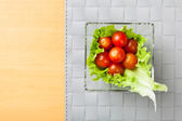Fresh vegetables on plate, grey place mat background — Stock Photo