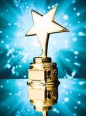 Gold star trophy against blue sparks background — Foto de Stock