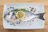 Gilt-head sea bream fish with spices on a platter — Stock Photo