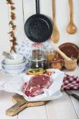 Raw steaks on the kitchen table — Stock Photo