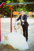 Beautiful young wedding couple in park, blonde bride on swing an — Stock Photo