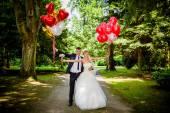 Bruid en bruidegom met ballonnen — Stockfoto