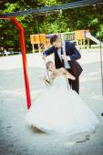 Wedding couple having fun on swing — Stock Photo