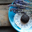 Dark chocolate truffle with lavender on a dessert plate and wooden background — Stock Photo #61174835