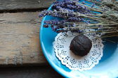 Dark chocolate truffle with lavender on a dessert plate and wooden background — Stock Photo