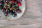 Fresh fruits background with sweet cherries on rustic wooden table — Stock Photo
