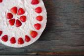 Background with raw strawberry cake on rustic wooden table — Stock Photo