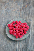 Raspberries on rustic wooden table — Stock Photo