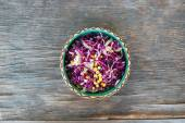 Fresh red cabbage salad with sweet corn in ceramic bowl on rustic wooden table — Stock Photo