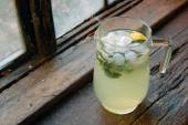 Fresh made lemonade with mint, with old wooden window background — Stock Photo