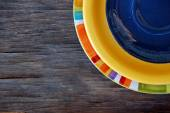 Colorful plates on wooden background — Stock Photo