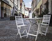 Beyaz Bahçe sandalye ve bir alışveriş caddesi tabloda — Stok fotoğraf