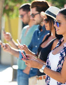 Portrait of group of friends having fun with smartphones. — Stok fotoğraf