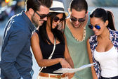 Group of friends use their map in the street. — Stock Photo