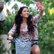 Pretty young girl riding bike and taking a selfie. — Stock Photo #52171359