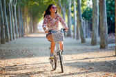 Pretty young girl riding bike in a forest. — Stock Photo