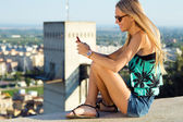 Beautiful blonde girl sitting on the roof with mobile phone. — Stock Photo