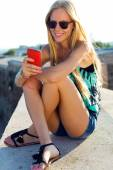 Beautiful blonde girl sitting on the roof with mobile phone. — Stock fotografie