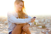 Beautiful girl sitting on the roof and listening to music. — Stok fotoğraf