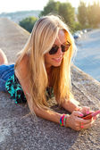 Beautiful blonde girl sitting on the roof with mobile phone. — Photo