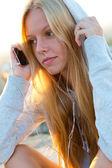 Vacker flicka sitter på taket och lyssna på musik. — Stock fotografie