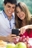 Couple using smart phone on romantic picinic. — Stock Photo