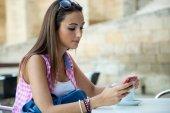 Menina bonita, bebendo café e mensagens de texto com o celular. — Fotografia Stock