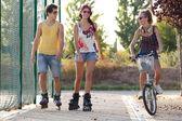 群好友一起溜冰鞋和在公园里骑自行车. — 图库照片