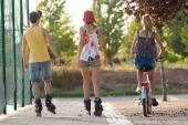 Group of friends with roller skates and bike riding in the park. — Stock Photo