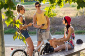 Group of friends with roller skates and bike riding in the park. — Stockfoto
