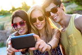 Group of friends taking a self portrait in the park. — Stock Photo