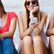 Three girls chatting with their smartphones at the park  — Stock Photo #54308941
