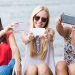 Three friends taking photos with a smartphone — Stock Photo #54309647