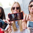 Three friends taking photos with a smartphone — Stock Photo #54309983