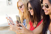 Three girls chatting with their smartphones at the park — Stock Photo