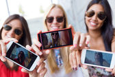 Three friends taking photos with a smartphone — Foto Stock