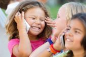 Group of childrens using mobile phones in the park. — Stock Photo