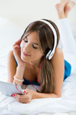Beautiful girl listening to music with tablet on sofa at home. — Stock Photo