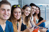 A group of students having fun with smartphones after class. — Stockfoto