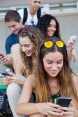 A group of students having fun with smartphones after class. — Zdjęcie stockowe