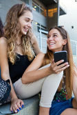 Two students having fun with smartphones after class. — Stock Photo