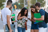 A group of students having fun with smartphones after class. — Stock fotografie
