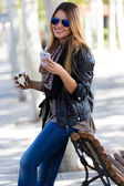 Portrait of beautiful girl drinking coffee and using her mobile  — Photo