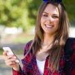 Portrait of beautiful girl using her mobile phone in city. — Stock Photo #56427845