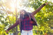 Portrait of beautiful girl standing in autumn field with arms raised. — Stock Photo