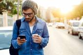 Modern young man with mobile phone in the street. — Stock Photo