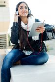 Beautiful girl listening to music in city.  — Stock Photo